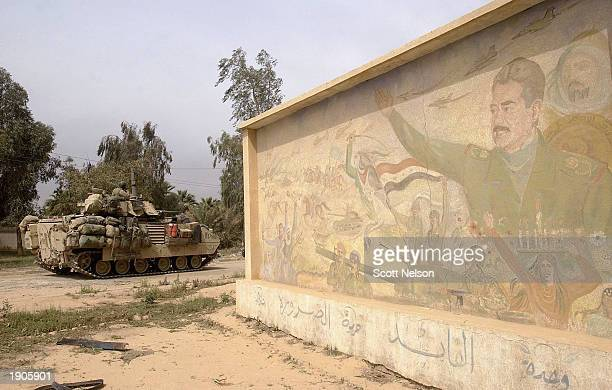 S Army 3rd Division 37 infantry Bradley fighting vehicle rolls past a Saddam Hussein mural as it conducts a neighborhood patrol on the outside...