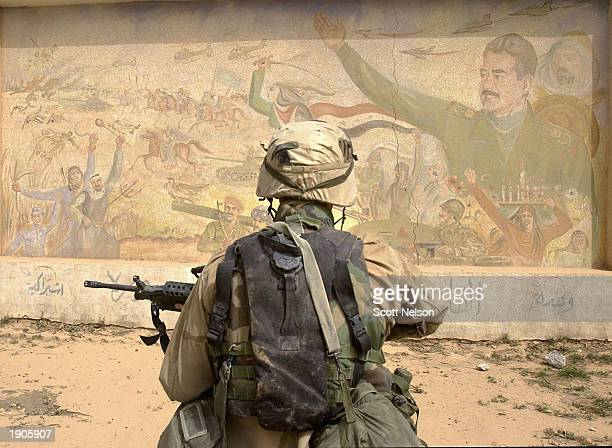 S Army 3rd Division 37 infantry soldiers examine a Saddam Hussein mural as they conduct a neighborhood patrol on the outside perimeter of the Baghdad...