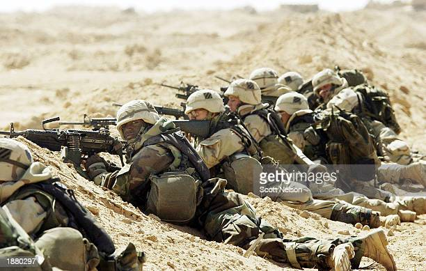 S Army 3rd Division 37 Infantry soldiers take cover after taking fire during a search and destroy mission March 27 2003 near the town of An Najaf...