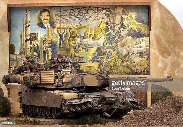 S Army 3rd Infantry M1A1 Abrams tank stands guard in front of a Saddam Hussein mural outside the nonoperational Daura Power Plant April 13 2003 in...