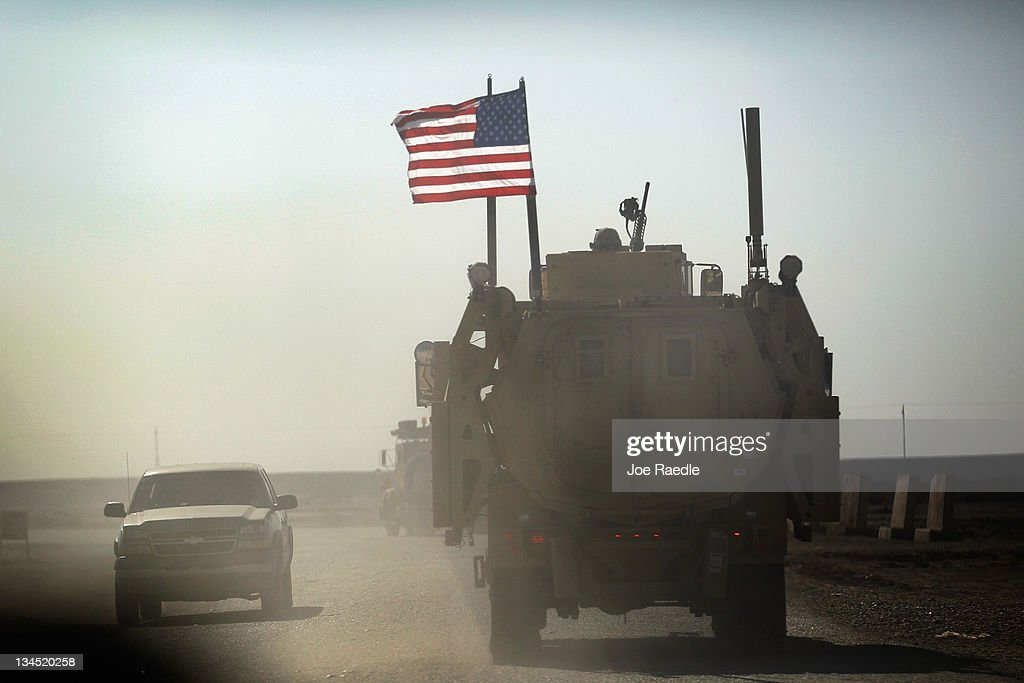 A U.S. Army armored vehicle flies an American flag as it provides security escort for a convoy of vehicles pulling equipment that is heading to Kuwait from Camp Adder as the Army continues to send it's soldiers and equipment home and the base is prepared to be handed back to the Iraqi government later this month on December 2, 2011 at Camp Adder, near Nasiriyah, Iraq. The United States military continues its pullout of the country by the end of this year, after eight years of war and the overthrow of Saddam Hussein.