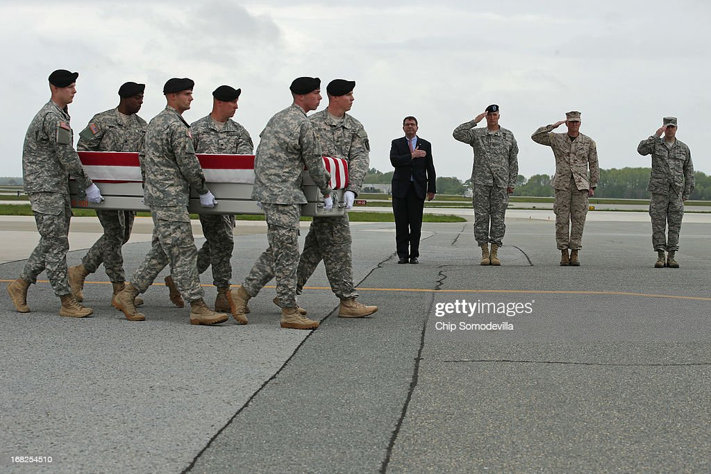 S. Army carry team carries the flag-draped transfer case with the remains of Army Staff Sgt. Francis Phillips IV, 28, of Meridan, New York, across the tarmac at Dover Air Force Base as (L-R) Deputy Secretary of Defense Ashton Carter, Army Maj. Gen. William Rapp, Marine Col. Christian Cabaniss and Air Force Col. John Devillier salute May 7, 2013 in Dover, Delaware. A member of the 1st Brigade Combat Team, 1st Armored Division, Phillips and four other soliders were killed May 4 when their vehicle hit a roadside bomb during a patrol in the Maiwand District in Kandahar Province, Afghanistan.