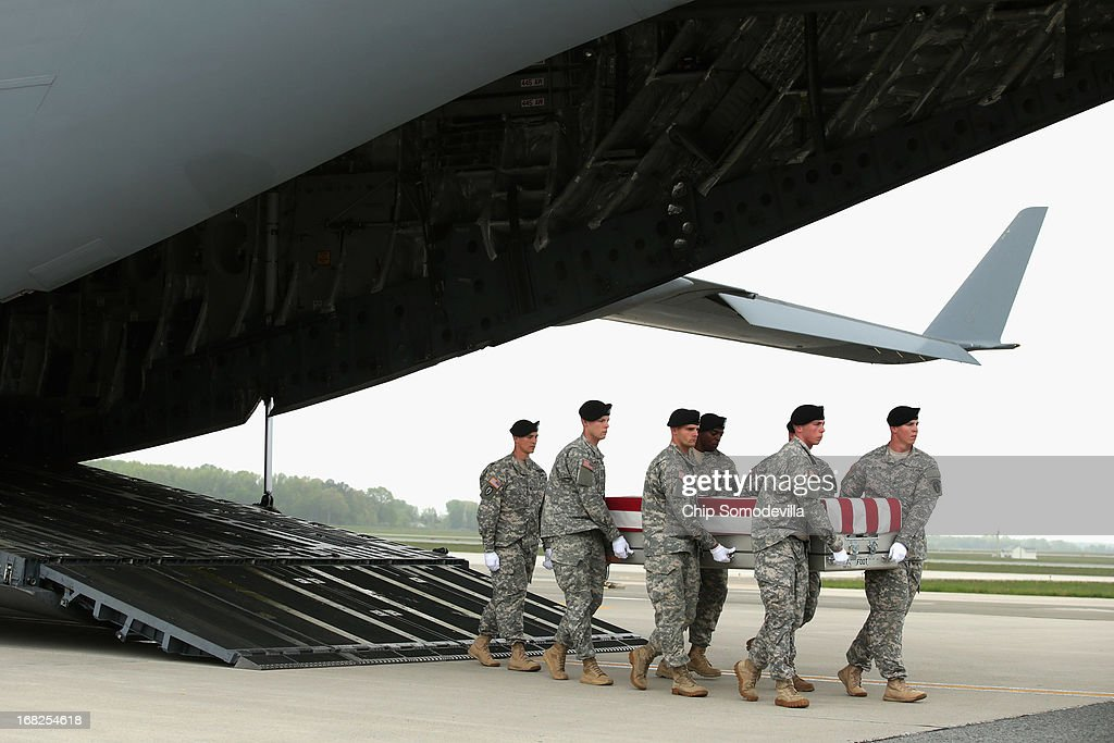 S. Army carry team carries the flag-draped transfer case with the remains of Army Spc. Thomas Paige Murach, 22, Meridian, Idaho off of a C-17 on the tarmac at Dover Air Force Base May 7, 2013 in Dover, Delaware. Assigned to the 1st Brigade Combat Team, 1st Armored Division, Murach and four other soliders were killed May 4 when their vehicle hit a roadside bomb during a patrol in the Maiwand District in Kandahar Province, Afghanistan.