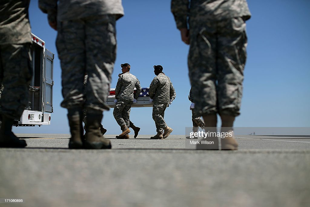 A U.S. Army carry team moves the transfer case containing the remains of U.S. Army Spc. Ember M. Alt, during a dignified transfer at Dover Air Force Base, on June 21, 2013 in Dover, Delaware. Spc. Alt 21, from Beech Island, S.C., was killed in Bagram , Afghanistan of wounds sustained after enemy forces attacked her unit at the air base there.