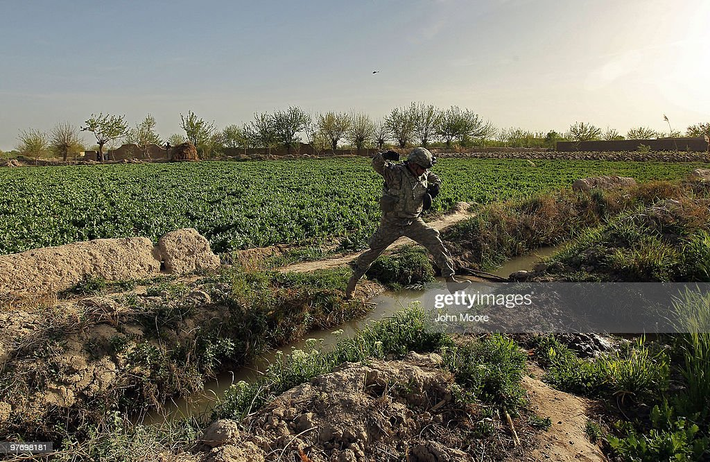 U.S. Army Chaplain Carl Subler jumps over an irrigation canal in an opium poppy field while on a military operation on March 14, 2010 at Howz-e-Madad in Kandahar province, Afghanistan. He had accompanied soldiers from the 2nd Battalion, 1st Infantry Regiment on an offensive operation against Taliban in the area. Although U.S. military chaplains are non-combatants, CPT. Subler goes on combat patrols to provide support for troops in the field. Military chaplains travel the battlefield throughout Afghanistan, providing a backbone of support for thousands of soldiers struggling with the difficulties of war and year-long deployments away from home.