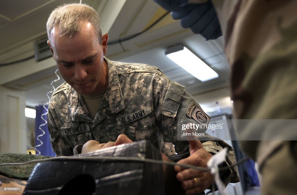U.S. Army Chaplain CPT. Loren Aderhold prays over a wounded American soldier at the military hospital on March 22, 2010 at Kandahar Airfield, Afghanistan. The 82nd Airborne soldier was injured when his vehicle was severely damaged in an IED blast in Kandahar province. U.S. military chaplains travel the battlefield across Afghanistan counseling, comforting and ministering to troops dealing with the difficulties of war and far from their families.