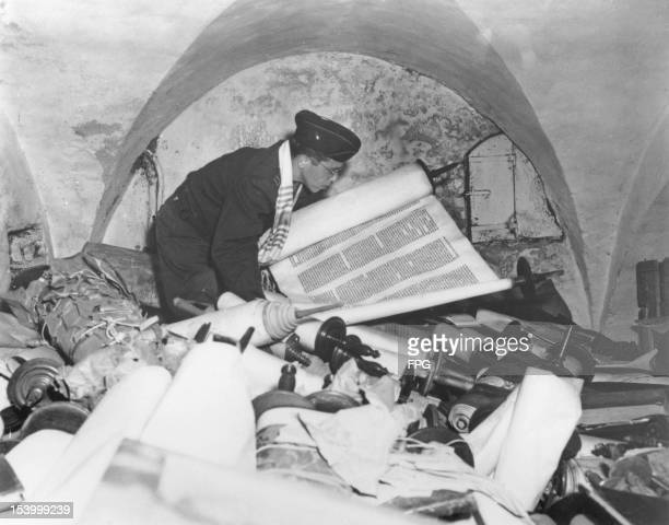 US Army chaplain Samuel Blinder examines one of hundreds of Jewish Sefer Torah scrolls stolen from all over Europe by Nazi forces and stored in the...
