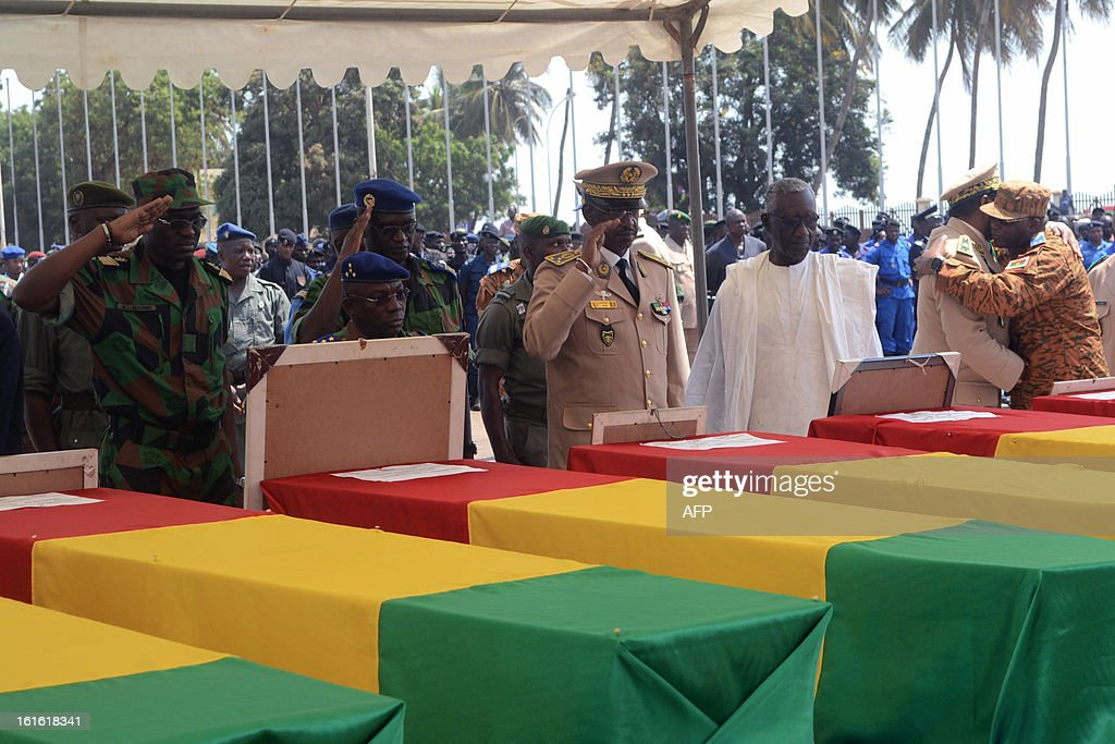 Army Chiefs of Staff of the ECOWAS pay their respect past the coffins of the victims of a plane carrying a military delegation from Guinea that crashed two days ago in the Liberian town of Charlesville, killing the army chief of staff and 10 other people, during a ceremony in Conakry on February 13, 2013.