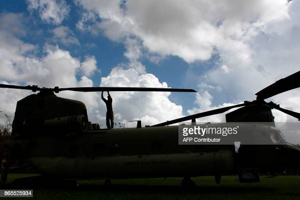 Army Chinook helicopter crewmember inspects the aircraft propellers before taking off from a mission to deliver supplies for residents affected by...