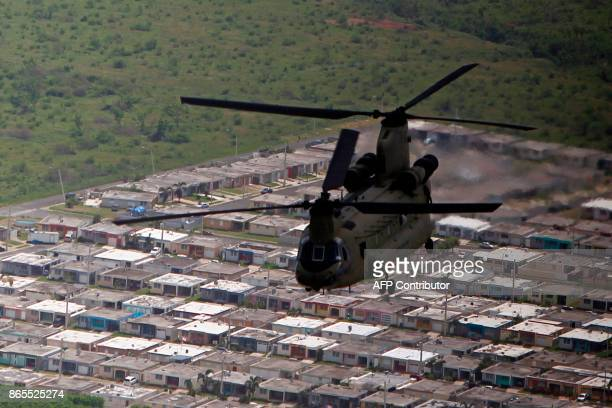 Army Chinook helicopter flies over Naguabo on its way to the town of Barranquitas with supplies for their residents affected by the passing of...