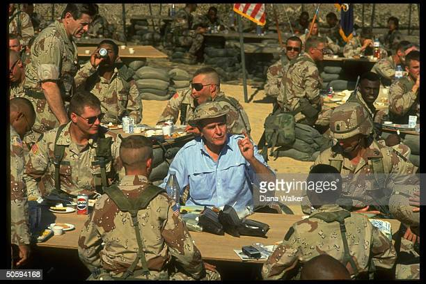 Army desertwear hatted Pres Bush opencollarcasualin heat eating desert feast w boys spending Thanksgiving w US gulf crisis troops