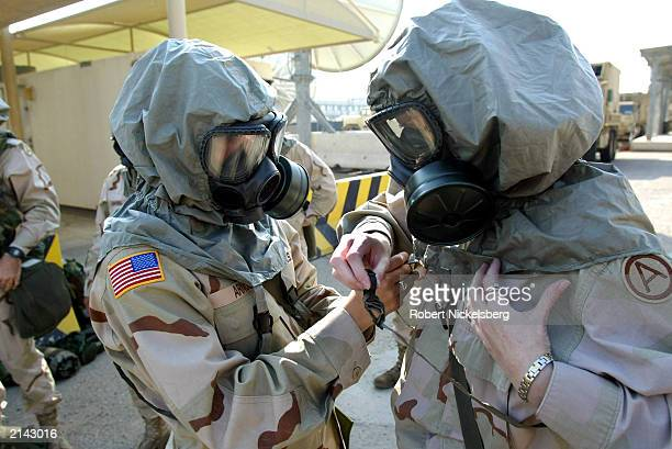 US Army female soldiers use the buddy system to assist each other in applying the NBC mask and hood during a Nuclear Biological Chemical training...
