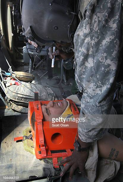 S Army flight medic SSG Rahkeem Francis with Dustoff Task Force Shadow of the 101st Combat Aviation Brigade helps injured Marine Sgt Jorge Mazon of...
