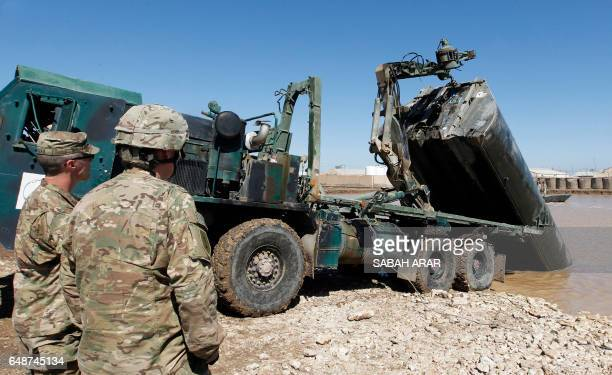 US army forces supervise during a training session at the Taji camp north of Baghdad with Iraqi soldiers aimed at preparing them to install floating...