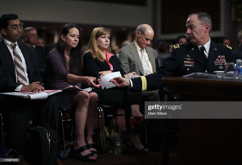 U.S. Army Gen. Keith Alexander (R), commander of the U.S. Cyber Command, director of the National Security Agency (NSA), passes a note to a aide during a Senate Appropriations Committee hearing on Capitol Hill, June 12, 2013 in Washington, DC. The committee is hearing testimony on President Obama's FY 2014 budget and Cybersecurity from Gen. Keith Alexander and other goverment officials.