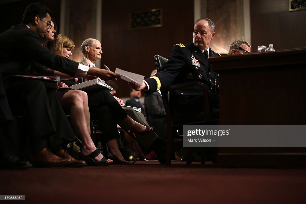 U.S. Army Gen. Keith Alexander (R), commander of the U.S. Cyber Command, director of the National Security Agency (NSA), is passed a note during a Senate Appropriations Committee hearing on Capitol Hill, June 12, 2013 in Washington, DC. The committee is hearing testimony on President Obama's FY 2014 budget and Cybersecurity from Gen. Keith Alexander and other goverment officials.