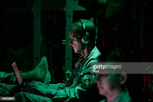 S Army Gen Stanley McChrystal the top US commander in Afghanistan works with his computer inside a C130 Hercules airplane on the way to Kabul after...