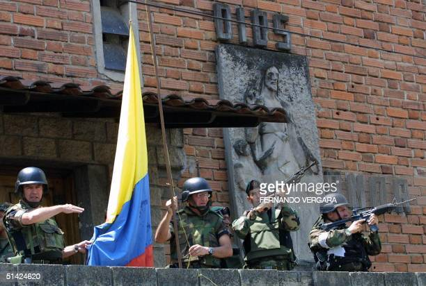 Army General Mario Montaya commander of the IV Infantry Brigade and General Carlos Alberto Ospina raise the Colombian flag 19 October 2002 look over...