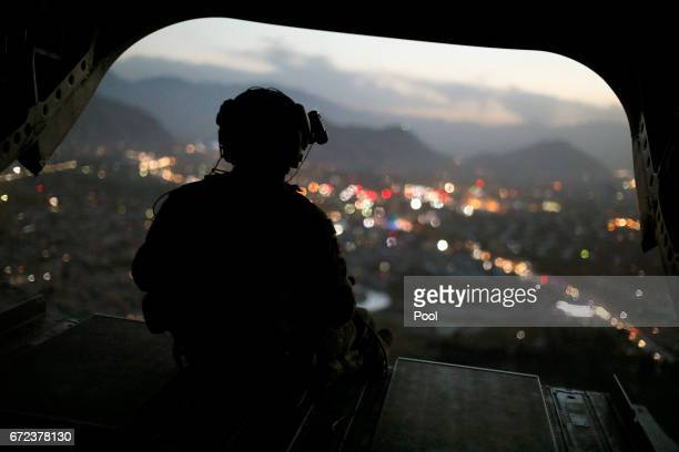S Army helicopter crewman mans a gun on the rear gate as it departs Resolute Support headquarters with US Defense Secretary James Mattis aboard April...