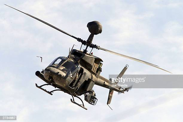 S Army helicopter flies above as a crane is used to remove the wreckage of one of the US Army Black Hawk helicopters on November 16 2003 after it...