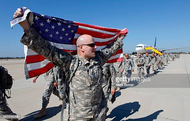 US Army helicopter pilot Joe McNamara drapes his flag over his shoulders and turns towards the crowds of family and friends assembled to greet the...