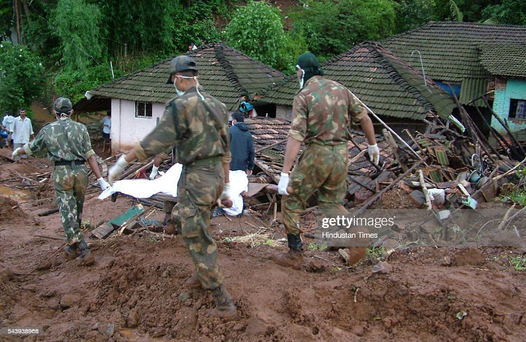 Army jawans carry body of a landslide victim in Jui village of Raigad District on July 29, 2005 in Mumbai, India.