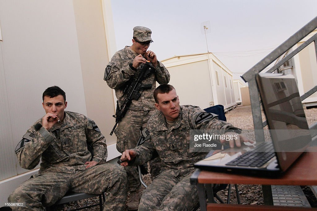 U.S. Army Lieutenant Christopher Molaro from Hawley, Pennsylvania, Lieutenant Patrick Mulvaney from Sugar Land, Texas and Lieutenant Adam Wilson from Ontario, California (L-R) of the 2-82 Field Artillery, 3rd Brigade, 1st Cavalry Division, smoke cigars and listen to music together as they wait for the orders to convoy to Kuwait from Camp Adder as the base is prepared to be handed back to the Iraqi government later this month on December 6, 2011 at Camp Adder, near Nasiriyah, Iraq. Camp Adder is one of the few bases remaining that the United States controls as America's military continues its pullout from the country by the end of this year after eight years of war.