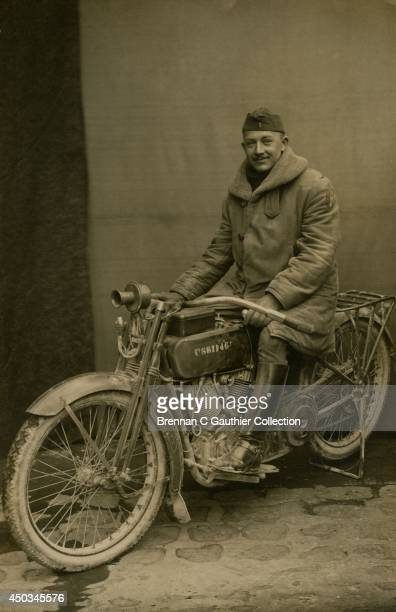 S Army Lieutenant sits astride a battleweary HarleyDavidson FUS dispatch motorcycle posed outside a French photo studio in the winter months...