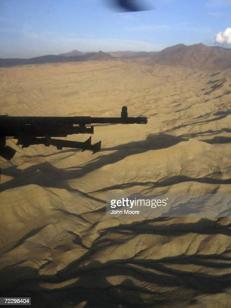 S Army machine gun points towards the rugged Afghan landscape from a Blackhawk helicopter as it flies over eastern Afghanistan near the volatile...