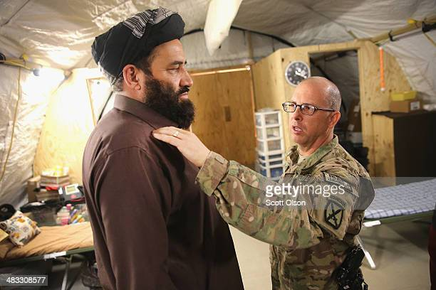 S Army Maj James Hart examines Haji Niyaz Mohammad Amirii provincial governor of Logar Province after he arrived at the field hospital on Forward...