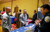 S Army Master Sgt Yeffiry Disla and US Army Sgt First Class Alvin Prado meet with a recruiter from the San Francisco police department during the...