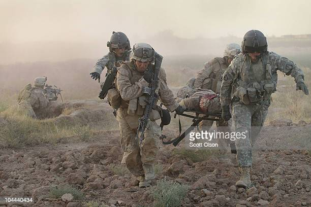 Army MEDEVAC helicopter crew members with Dustoff Task Force Shadow of the 101st Combat Aviation Brigade help Marines carry a severely wounded Marine...
