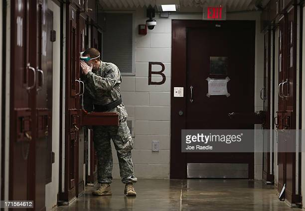 A US Army Military Police checks in on a detainee during morning prayer at Camp V in the US military prison for 'enemy combatants' on June 26 2013 in...
