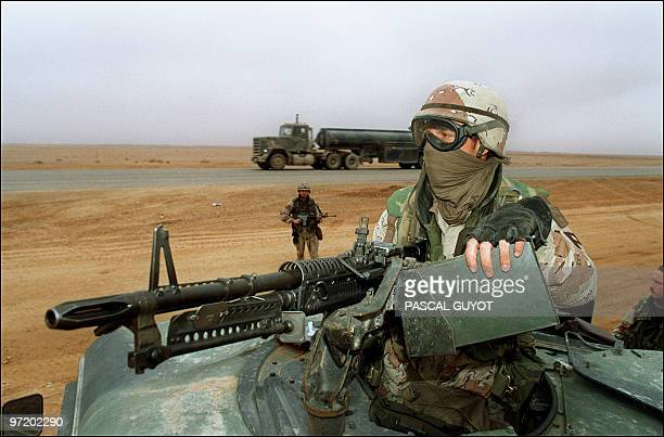 A US army MP stands guard atop his vehicle during a stop over of his convoy as a truck drives along the main road in north eastern Saudi Arabia 21...