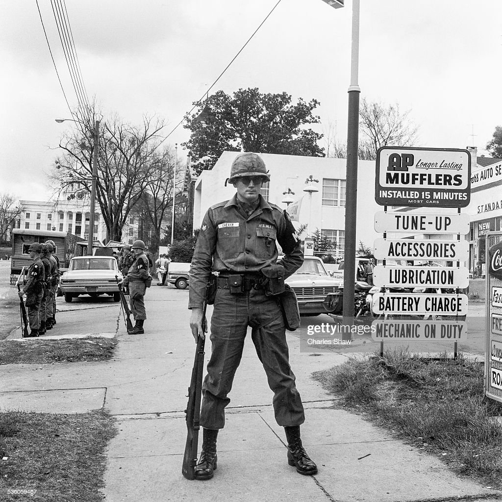 US Army MPs stand guard on Dexter Avenue on the day that the Selma to Montgomery March arrived at the Alabama State Capitol (at center rear) later in the day, Montgomery, Alabama, March 25, 1965. Mostly obscured, at right rear, is the Dexter Avenue Baptist Church which served as headquarters for Martin Luther King Jr during the Montgomery Bus Boycott (1955 - 1956); King had been Pastor of the church between 1954 to 1960.