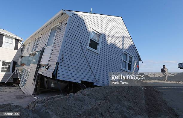 S Army National Guard Sgt Martin McGhee walks past a home ravaged by Superstorm Sandy on November 5 2012 in Long Beach Township New Jersey Today was...