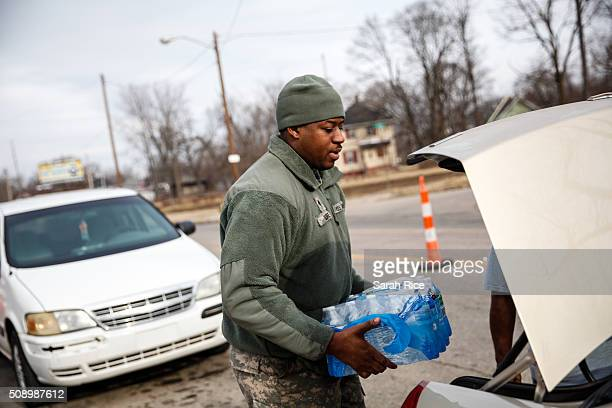 Army National Guard Spc Terence Burse carries bottled water out to the car for a resident on February 7 2016 in Flint Michigan Months ago the city...