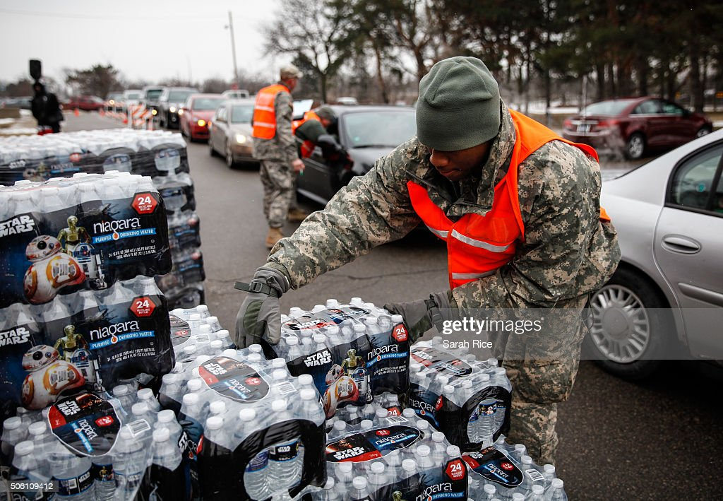 Army National Guard Specialist David Brown loads bottled water into waiting cars at a fire station on January 21 2016 in Flint Michigan Residents can...