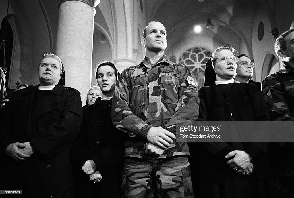 Army officer joins nuns in the congregation for midnight mass in a Sarajevo church on Christmas night. During the 47 months between the spring of 1992 and February 1996, the people of Sarajevo endured the longest siege Europe has witnessed since the end of the Second World War. More than 10,600 people were killed with a further 56,000 wounded or maimed.