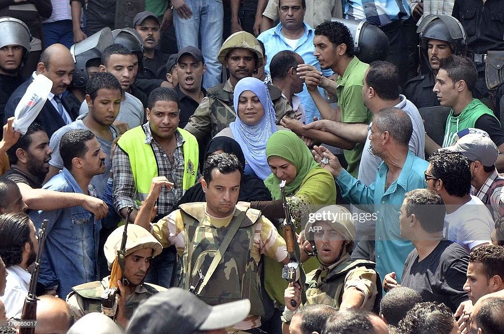 Army officers escort an Islamist women out of Cairo's Al-Fath mosque where Islamist supporters of ousted president Mohamed Morsi held up on August 17, 2013. The standoff at al-Fath mosque in central Ramses Square began on August 16, with security forces surrounding the building where Islamists were sheltering and trying to convince them to leave.