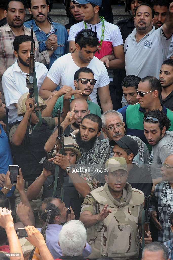 Army officers escort people out of Cairo's Al-Fath mosque where Islamist supporters of ousted president Mohamed Morsi held up on August 17, 2013. The standoff at al-Fath mosque in central Ramses Square began on August 16, with security forces surrounding the building where Islamists were sheltering and trying to convince them to leave.