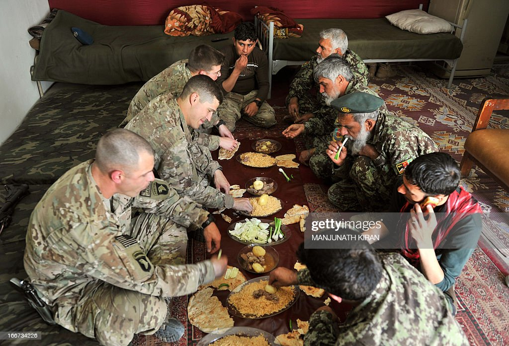 US Army officers (left row) of team Heavy Metal of the Security Forces Advisory and Assistance Team 6 (SFAAT6) belonging to the Combined Team Bastogne, 1st Brigade Combat Team, 101st Airborne Division (Air Assault), at a luncheon meeting hosted by Afghan National Army's (ANA) HHC Commander of Kandak 6, Captain Hasan Khan at the forward base Honaker Miracle at Watahpur District in Kunar province on April 16, 2013. Budget cuts and war fatigue in Western capitals mean the 100,000 soldiers left serving in NATO's International Security Assistance Force are packing up and taking off as the mission prepares to close next year. AFP PHOTO/Manjunath KIRAN