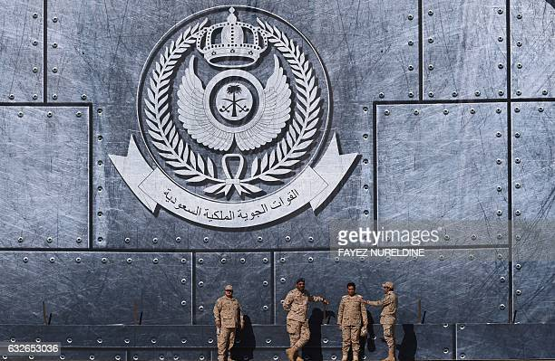 TOPSHOT Army officers stand under the Saudi Air Force logo during a ceremony marking the 50th anniversary of the creation of the King Faisal Air...