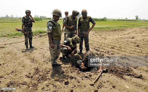 Army personals checking the spot after defusing mortar shells fired by Pakistani rangers targeting 15 border outposts and several border hamlets on...