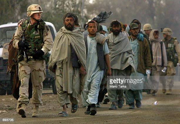 Army personnel escort Afghan laborers on the American military compound at Kandahar Airport January 13 2002 in Kandahar Afghanistan The laborers...