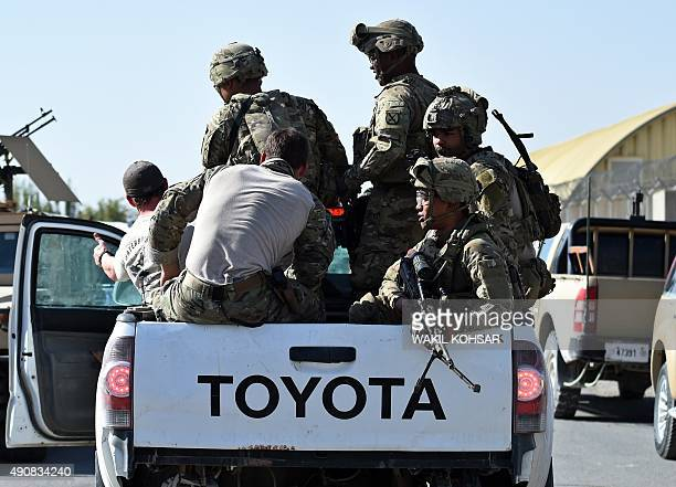 US army personnel ride in a truck inside an Afghan military base during fighting between Taliban militants and Afghan security forces in Kunduz on...