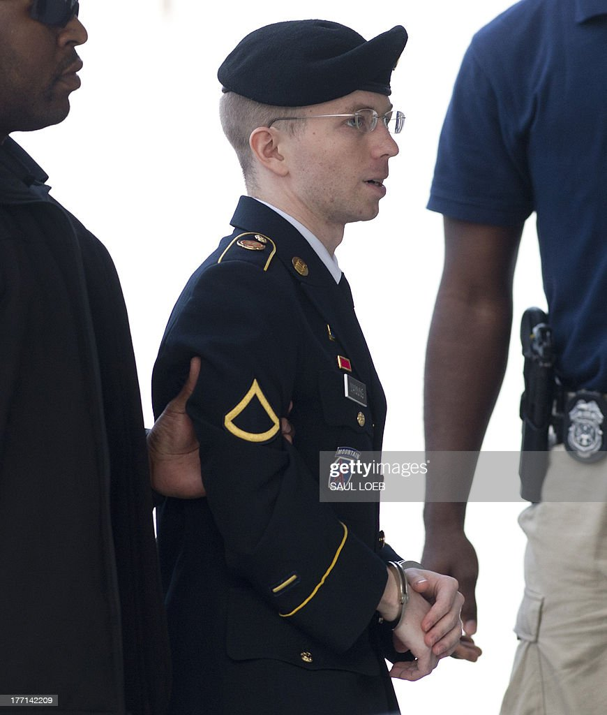 US Army Private First Class Bradley Manning arrives alongside military officials at a US military court facility to hear his sentence in his trial at Fort Meade, Maryland on August 21, 2013. A sentencing decision will be announced later Wednesday. AFP PHOTO / Saul LOEB