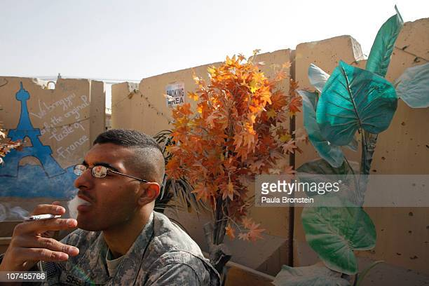 Army Private First Class Michael Shelton smokes after lunch at La Patisserie french cafe along the boardwalk at Kandahar Air Field December 8 2010 in...