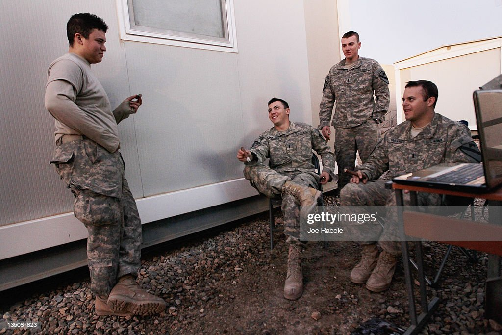 U.S. Army Private Steven Villalobos from Wheeling, Illinois, Lieutenant Christopher Molaro from Hawley, Pennsylvania, Lieutenant Adam Wilson from Ontario, California and Lieutenant Patrick Mulvaney from Sugar Land, Texas (L-R) of the 2-82 Field Artillery, 3rd Brigade, 1st Cavalry Division, smoke cigars and listen to music together as they wait for the orders to convoy to Kuwait from Camp Adder as the base is prepared to be handed back to the Iraqi government later this month on December 6, 2011 at Camp Adder, near Nasiriyah, Iraq. Camp Adder is one of the few bases remaining that the United States controls as America's military continues its pullout from the country by the end of this year after eight years of war.