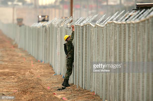 Army Ranger helps his unit erect a chainlink fence that will be topping with barbed wire parallel to the primary steel US/Mexico border fence to...